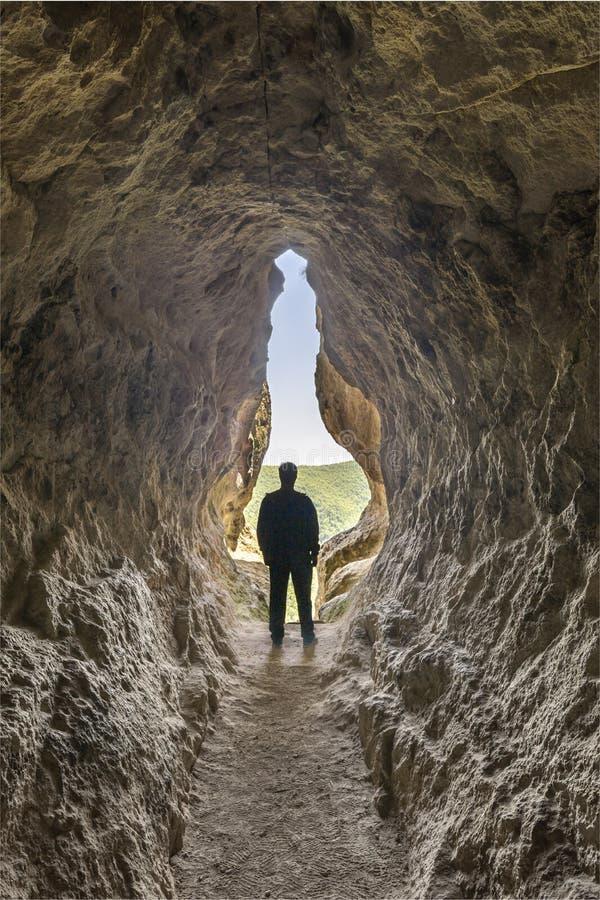 Silhueta do homem na extremidade de uma caverna pequena imagens de stock royalty free
