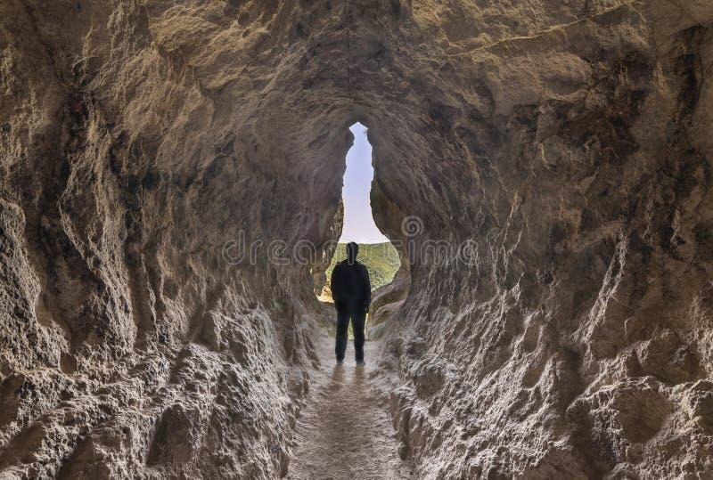 Silhueta do homem na extremidade de uma caverna pequena foto de stock