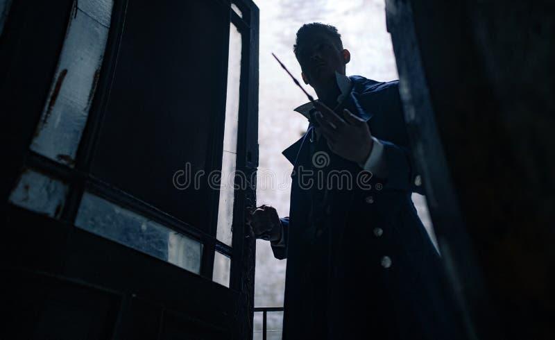 Silhueta do homem na imagem do mágico preto com a varinha mágica em sua mão fotografia de stock