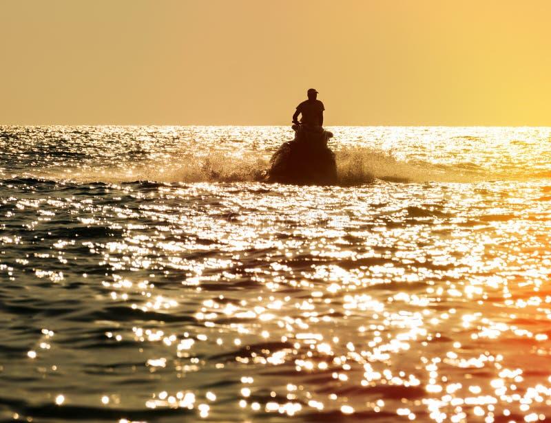 Silhueta do homem no esqui do jato no mar fotografia de stock