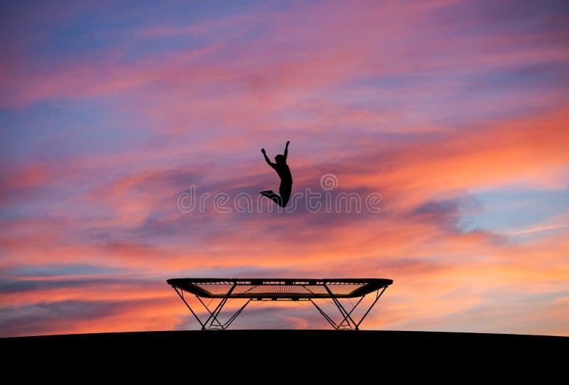 Silhueta do homem no trampolim no por do sol fotos de stock royalty free