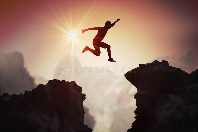 Silhueta do homem novo que salta sobre montanhas e penhascos no por do sol fotos de stock