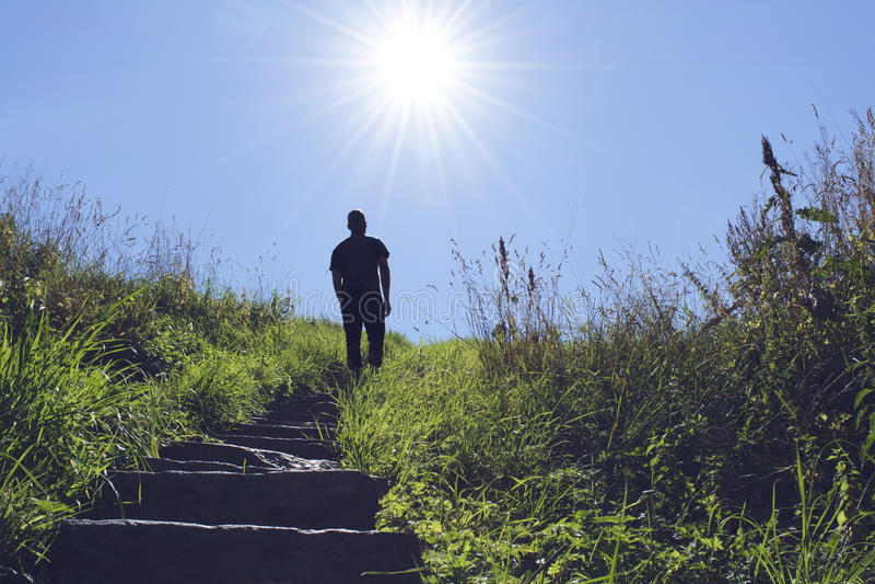 Silhueta do homem que anda acima de uma escada para o sol imagens de stock royalty free