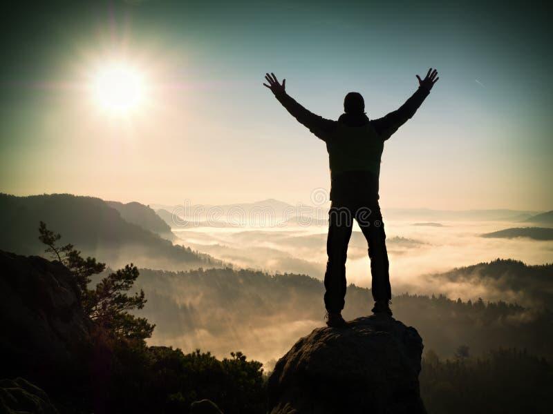Silhueta do homem que escala altamente no penhasco O caminhante escalado até o pico aprecia a vista imagens de stock