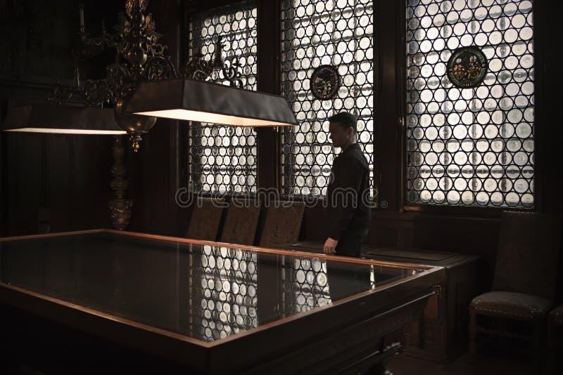Silhueta do homem que está por uma tabela grande em uma casa velha Janelas Leaded que deixam na luz de trás o foto de stock
