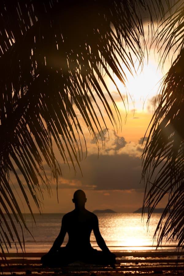 Silhueta do homem que faz o exercício da ioga imagens de stock