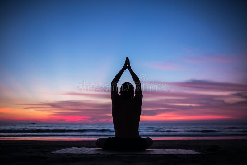 Silhueta do homem que faz o exercício da ioga no por do sol foto de stock royalty free