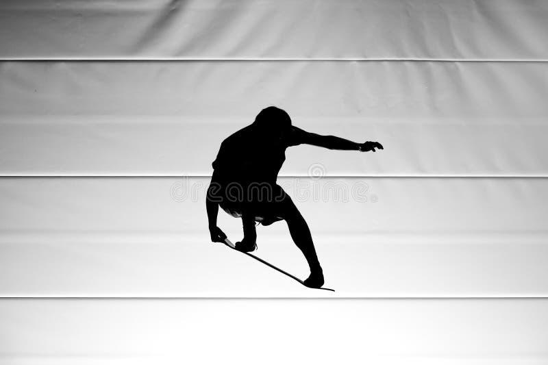 Silhueta do homem que salta com plataforma do skate fotografia de stock
