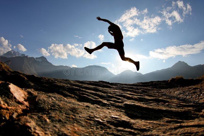 Silhueta do homem que salta em alpes suíços foto de stock