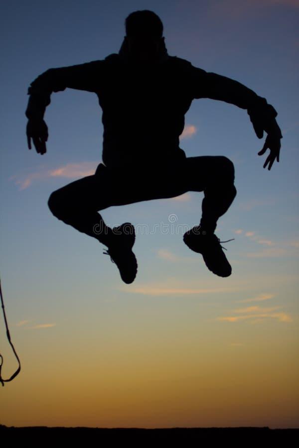 Silhueta do homem que salta no fundo do por do sol foto de stock royalty free