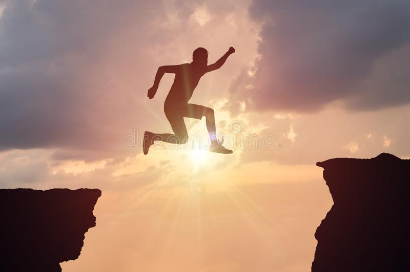 Silhueta do homem que salta sobre uma diferença no por do sol fotos de stock