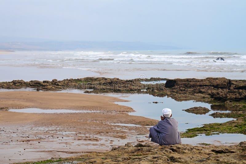 Silhueta do homem que senta-se na frente do oceano foto de stock