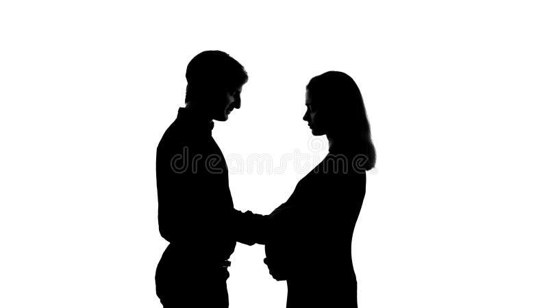 Silhueta do homem que toca em sua barriga grávida da esposa, família feliz, de maternidade fotografia de stock royalty free