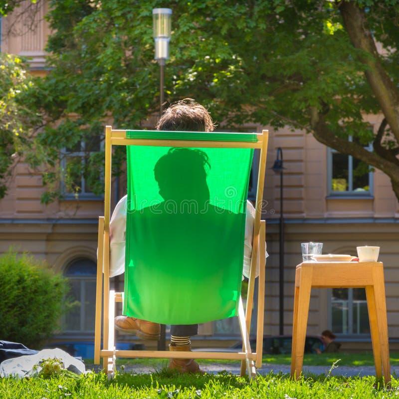 Silhueta do homem relaxado no deckchair em um parque imagens de stock royalty free