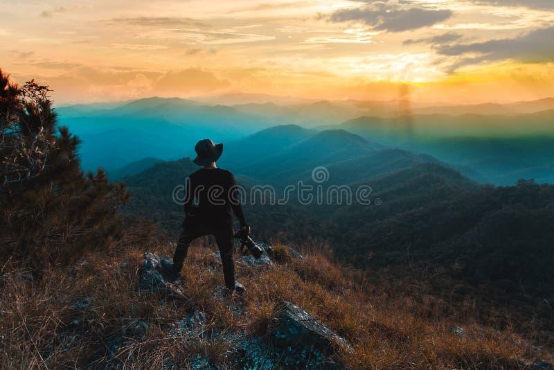 A silhueta do homem sustenta as m?os no pico da montanha, conceito do sucesso imagens de stock royalty free