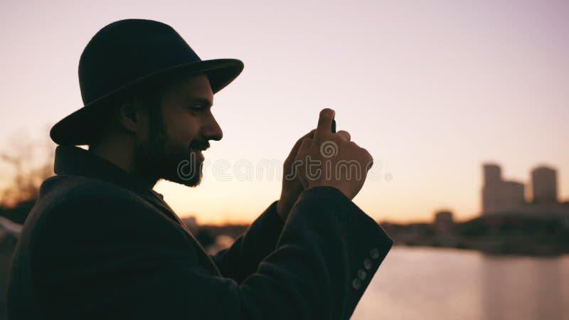 Silhueta do homem do viajante no chapéu que toma a foto panorâmico da skyline da cidade em sua câmera do smartphone no por do sol fotos de stock royalty free
