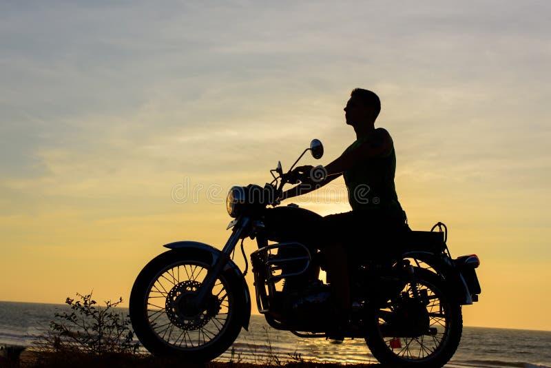 Silhueta do indivíduo na motocicleta no fundo do por do sol O motociclista novo está sentando-se na motocicleta, cara no perfil V imagem de stock