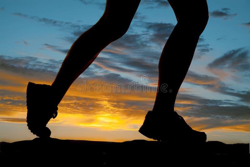 Silhueta do lado do funcionamento dos pés da mulher fotos de stock