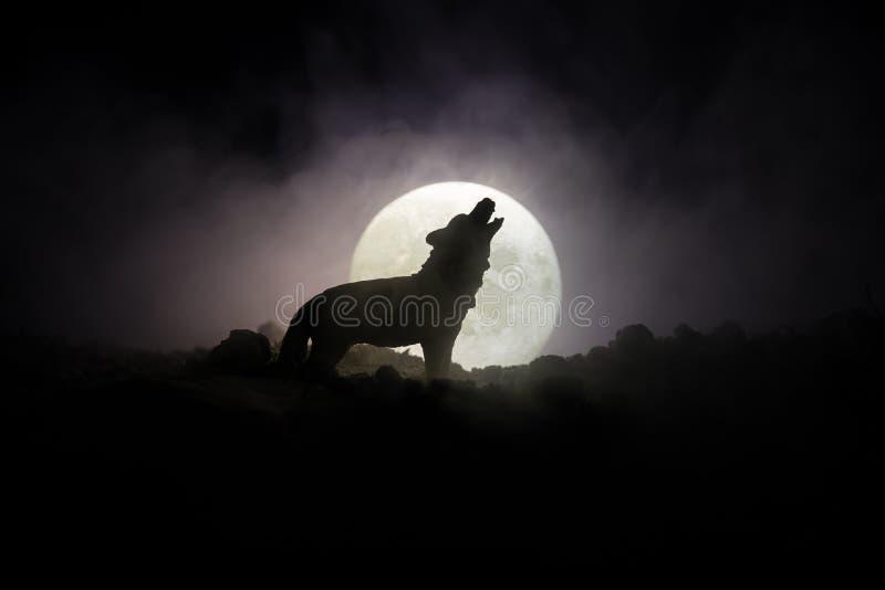 Silhueta do lobo do urro contra o fundo escuro e Lua cheia ou lobo nevoento tonificado na silhueta que urram ao máximo a lua hall foto de stock