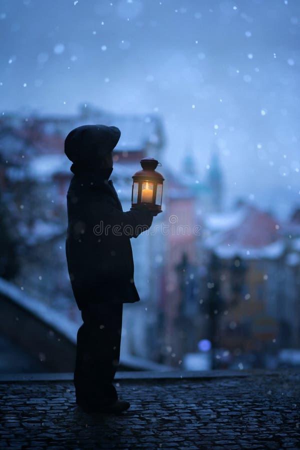 Silhueta do menino, estando nas escadas, guardando a lanterna, vista de imagens de stock royalty free