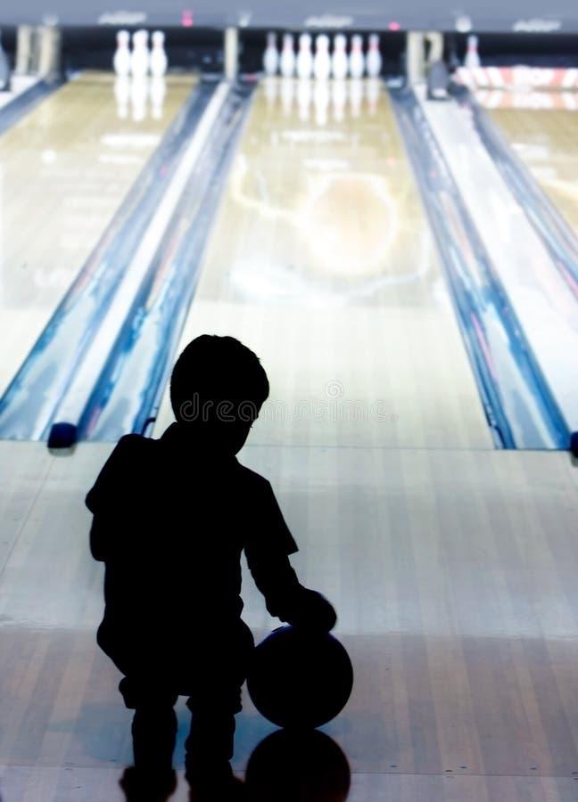 Silhueta do menino novo no bowling fotografia de stock royalty free