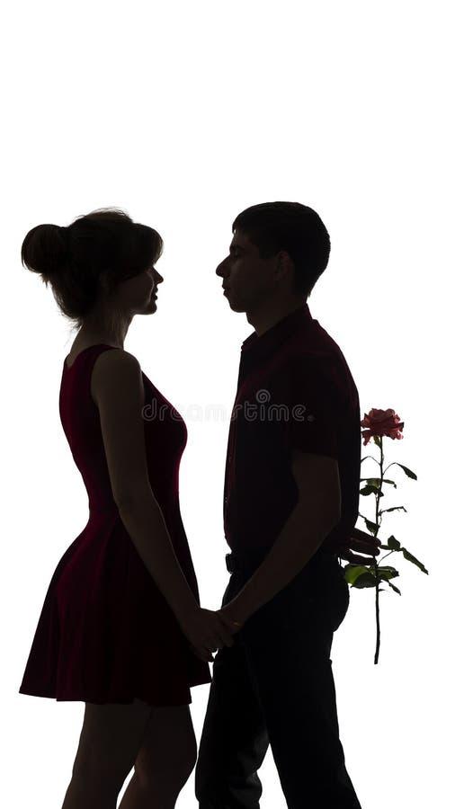 A silhueta do menino que guarda uma caixa de presente com uma curva atrás dela de volta a felicita a menina, um par novo no amor  imagem de stock