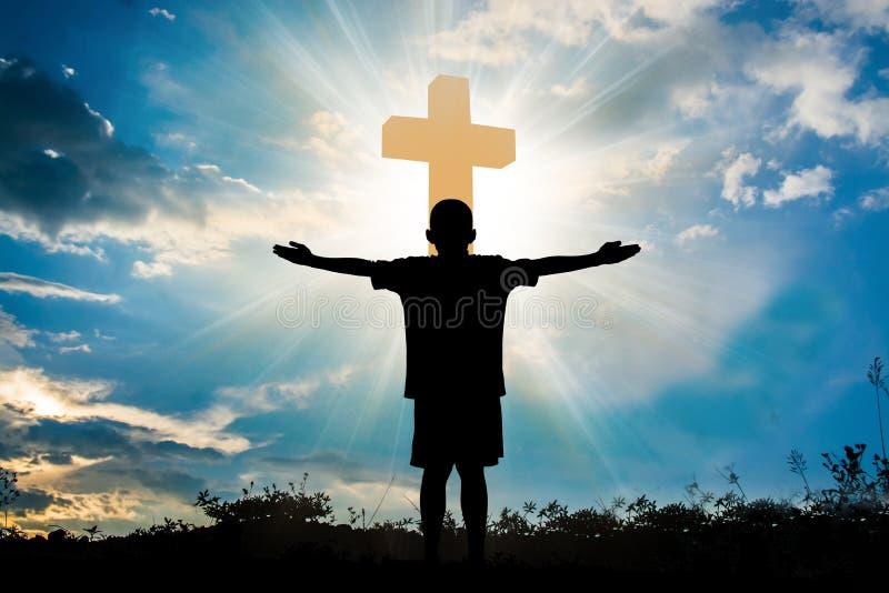 Silhueta do menino que reza a uma cruz com cloudscape celestial SU fotografia de stock royalty free