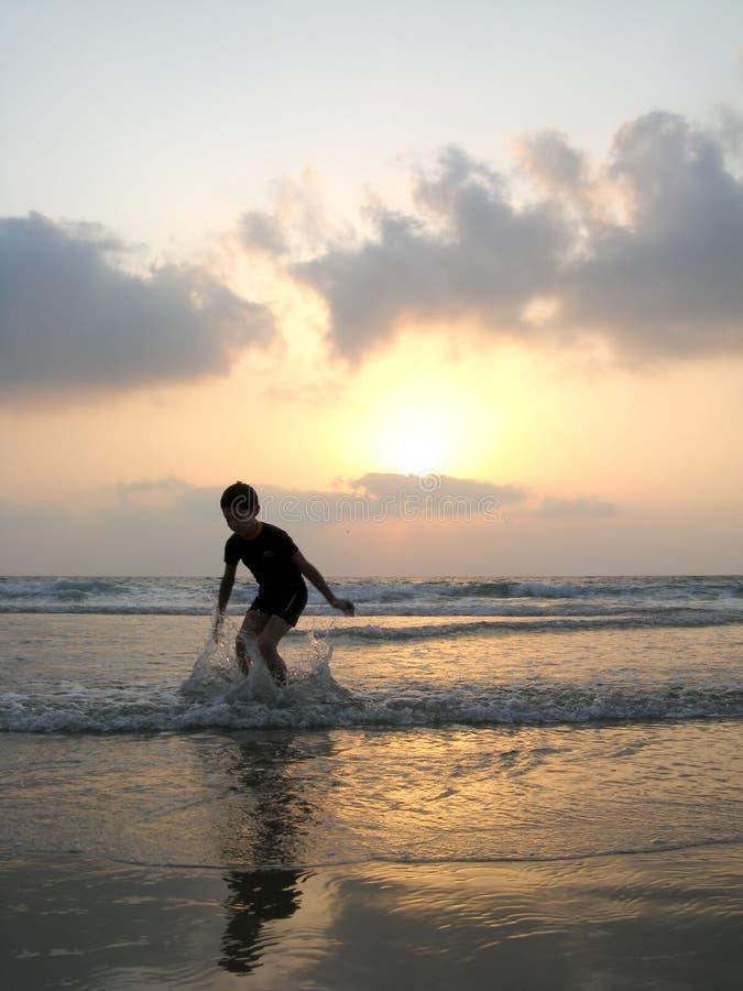 Silhueta do miúdo na praia imagem de stock