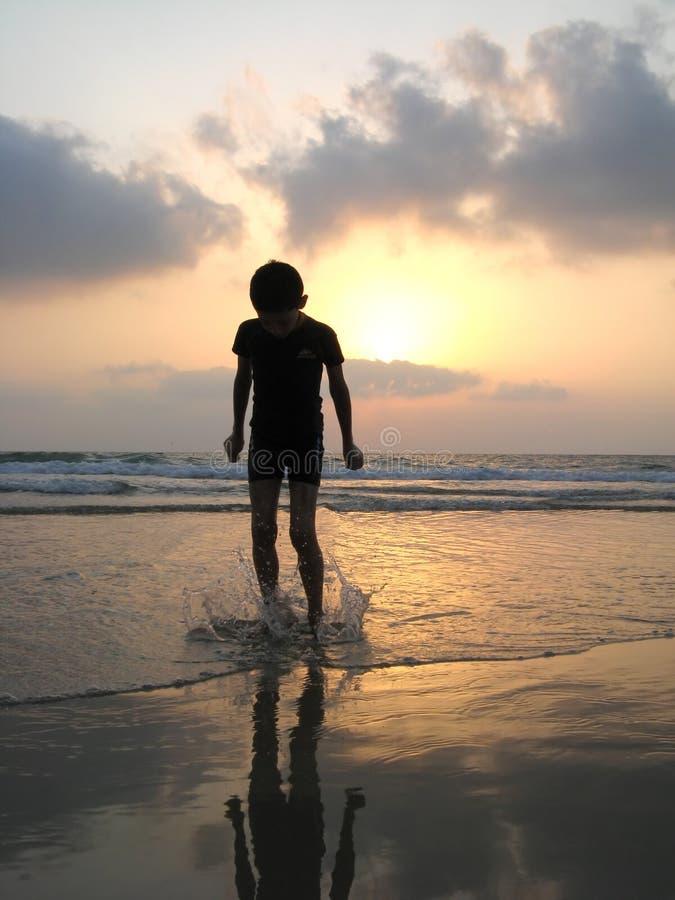 Silhueta do miúdo na praia imagens de stock
