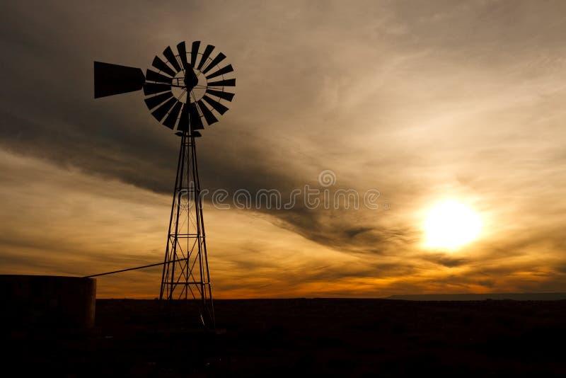 Silhueta do moinho de vento da exploração agrícola no por do sol imagem de stock