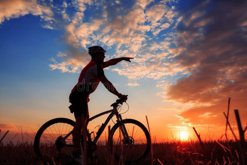 Silhueta do motociclista da montanha no nascer do sol fotografia de stock