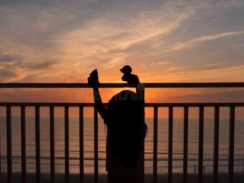 Silhueta do nascer do sol de observação da menina fotografia de stock royalty free