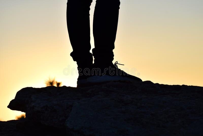 Silhueta do pé humano no fundo do monte quando por do sol fotografia de stock