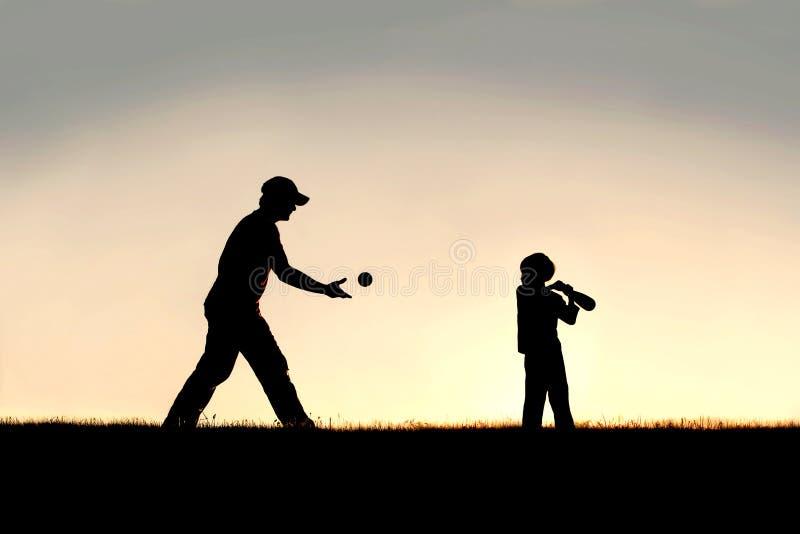 Silhueta do pai e da jovem criança que jogam o basebol fora fotografia de stock