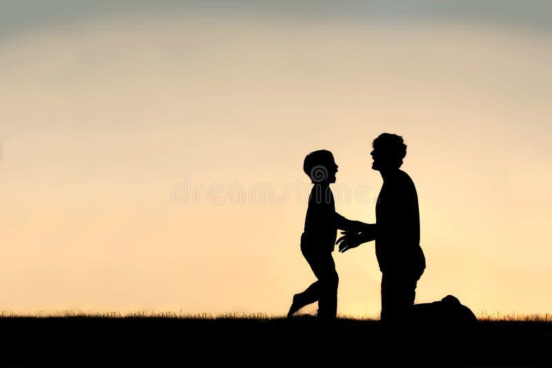 Silhueta do pai e do filho felizes no por do sol foto de stock