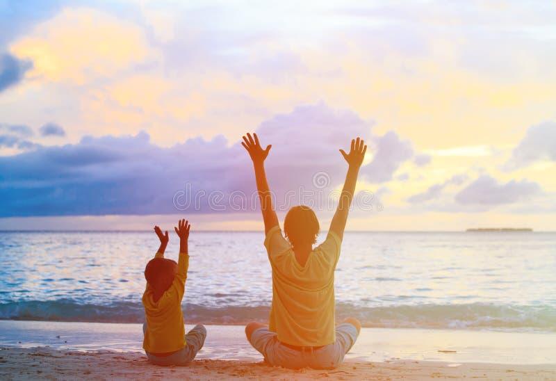Silhueta do pai e do filho felizes no por do sol fotografia de stock