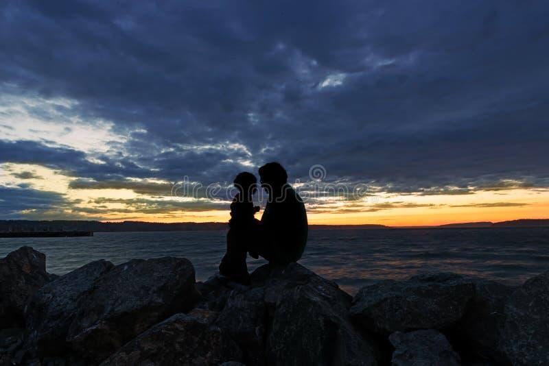 Silhueta do pai e do filho que apreciam o por do sol fotos de stock royalty free