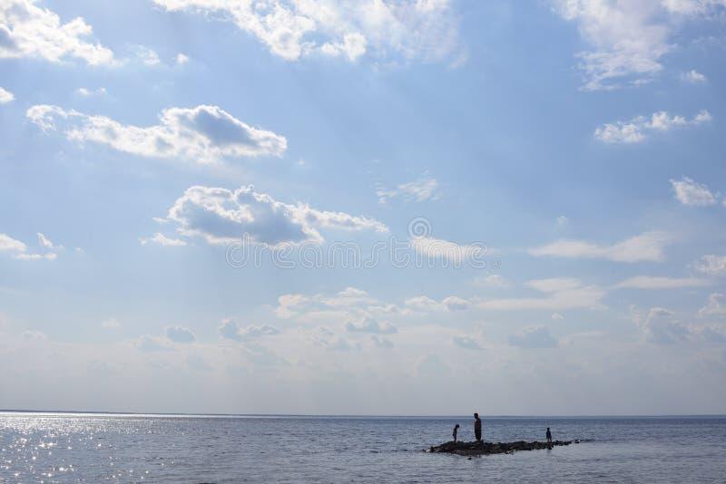Silhueta do pai e dos dois poucos filhos em uma ilha pequena no mar foto de stock