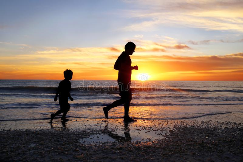 Silhueta do pai e seu filho novo que movimenta-se na praia junto no por do sol imagens de stock