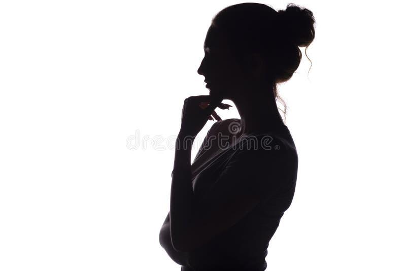 Silhueta do perfil de uma menina pensativa com uma mão no queixo, uma jovem mulher em um fundo isolado branco imagem de stock royalty free