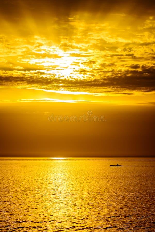 Silhueta do pescador no barco no por do sol fotos de stock royalty free
