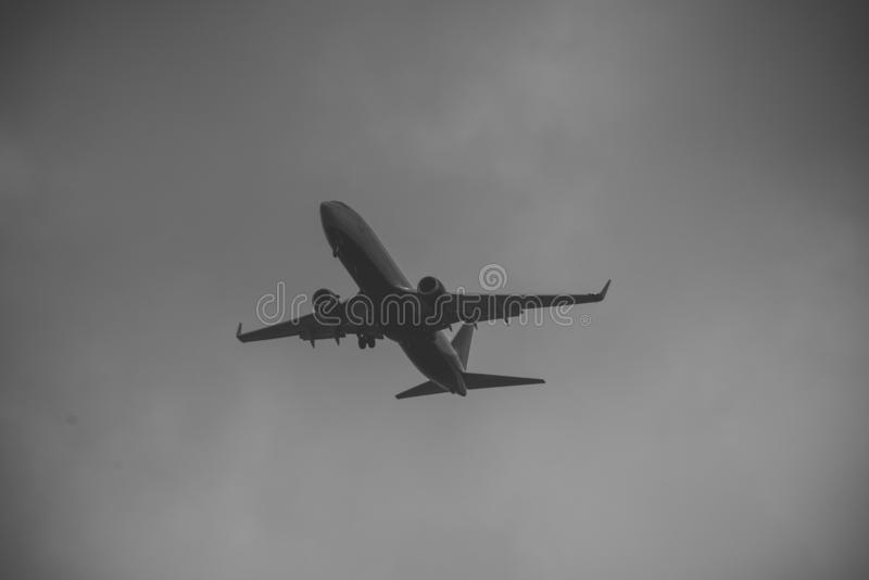 Silhueta do plano no céu cinzento O avião comercial voa a elevação no céu, voo Voos internacionais, entrega imagens de stock royalty free
