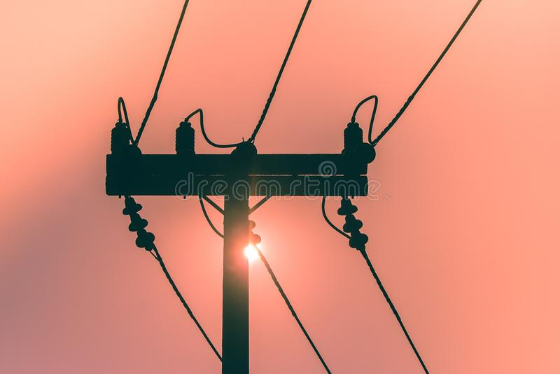 Silhueta do polo da eletricidade e da linha elétrica da alta tensão com o por do sol no fundo fotografia de stock royalty free