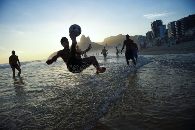 Silhueta do pontapé de bicicleta que joga o Rio do futebol da praia de Altinho imagens de stock royalty free