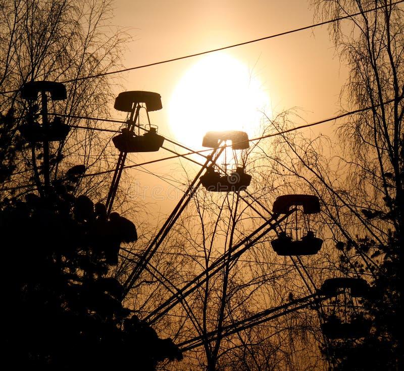 Silhueta do por do sol da cabine da roda de Ferris cercada por ramos de árvore despidos imagem de stock royalty free