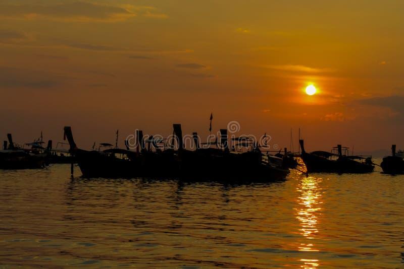 Silhueta do por do sol dos barcos de pesca na estância de verão do mar em Tailândia, em Krabi, em Railey e em Tonsai imagem de stock royalty free