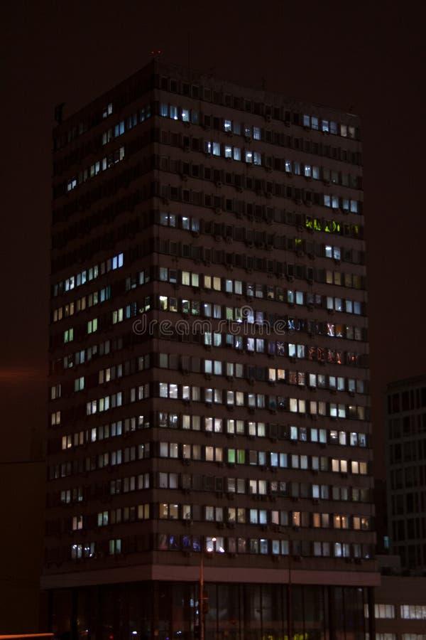 Silhueta do prédio de escritórios com reflexões das luzes de rua imagens de stock