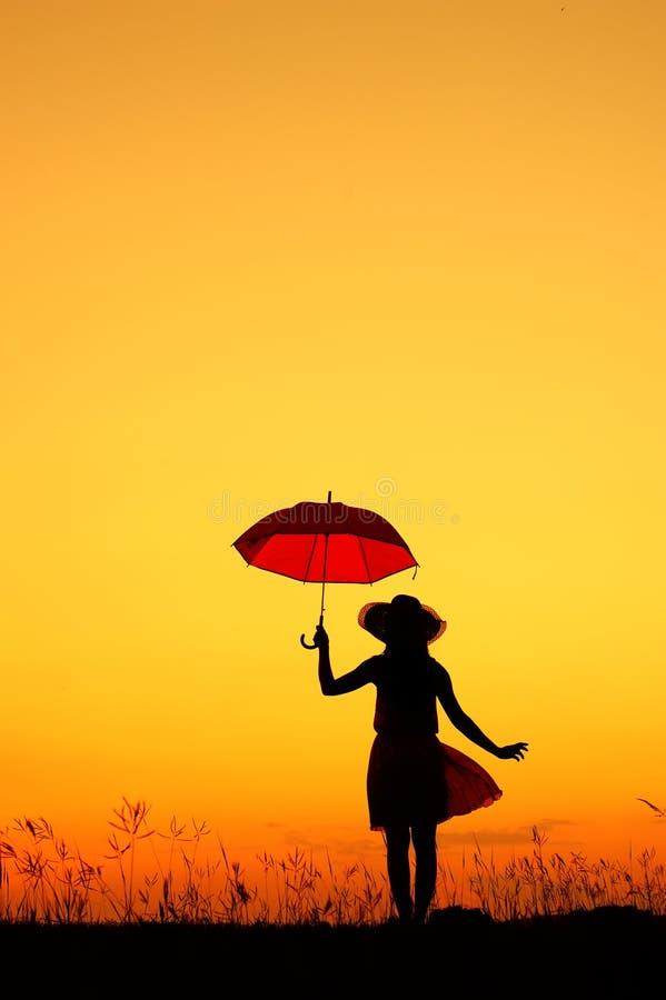 Silhueta do salto e do por do sol da mulher do guarda-chuva foto de stock