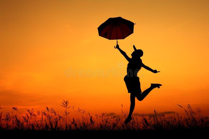 Silhueta do salto e do por do sol da mulher do guarda-chuva imagens de stock royalty free