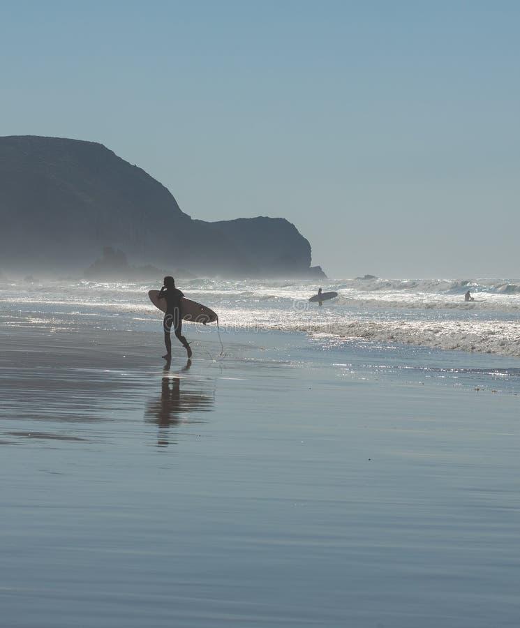 Silhueta do surfista na praia do oceano imagem de stock